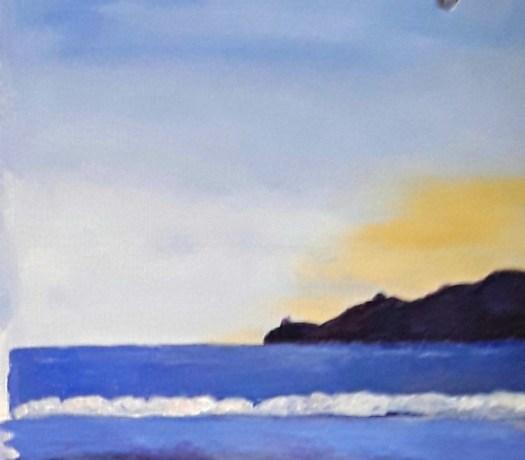 A hint of the sunrise behind a headland in a calm seascape.