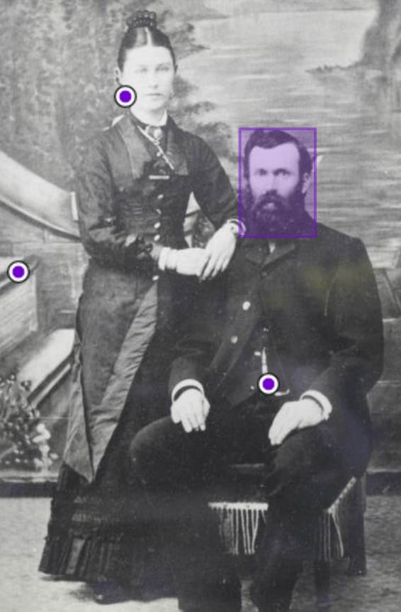 Black and white photograph of man seated with woman standing next to him. The photo has purple dots indicating it has been annotated.