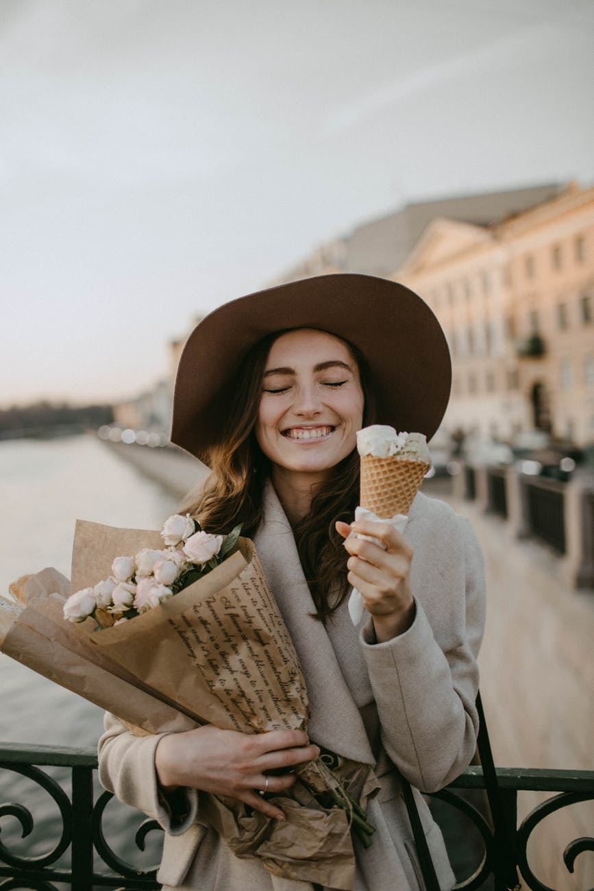 woman wearing brown coat holding white flower bouquet and ice cream