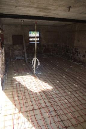 Die Armierung und Heizungskabel, in der Mitte kommt der Anschluss empor, an den dann ein Thermostat angeschlossen wird