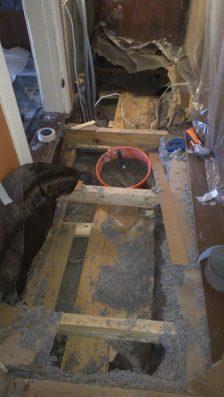 Beim Mauern: man sieht Teile des Unterbodens und darunter die Betondecke des Kellers
