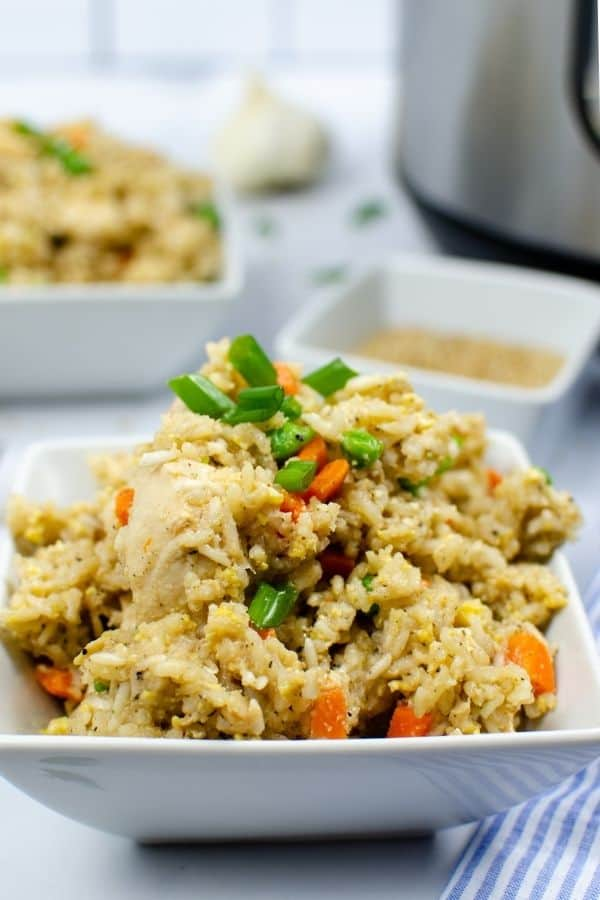 chicken fried rice cooked in the Instant Pot, piled into a white square bowl and topped with green onions