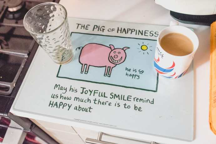 A morning cuppa rests on an Edward Monkton 'Pig of Happiness' mat