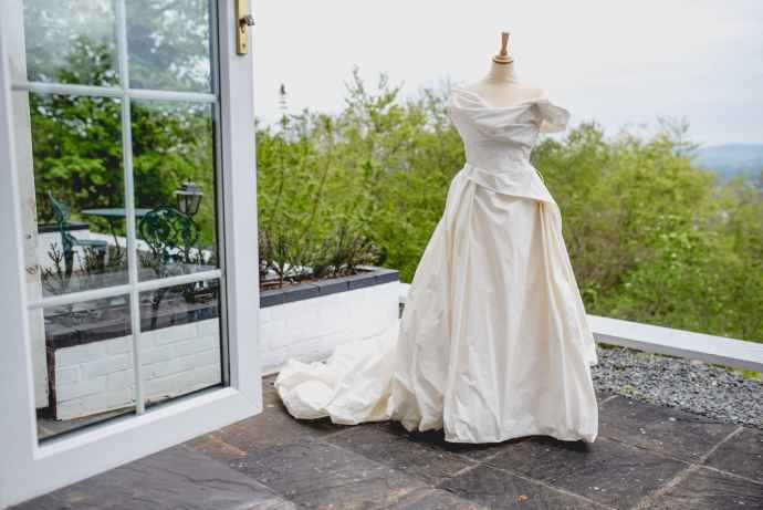 Hatty's raw silk wedding gown is displayed on a mannequin on an outdoor terrace