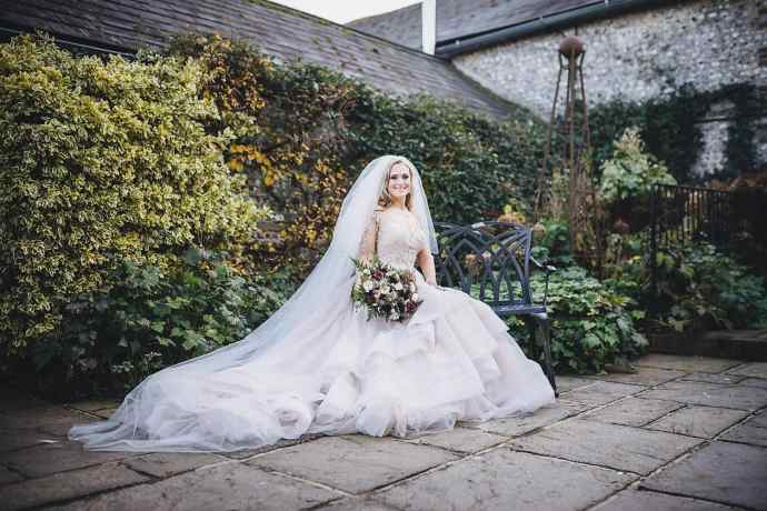 The bride sits on a wrought iron bench as her Martina Liana gown flows around her