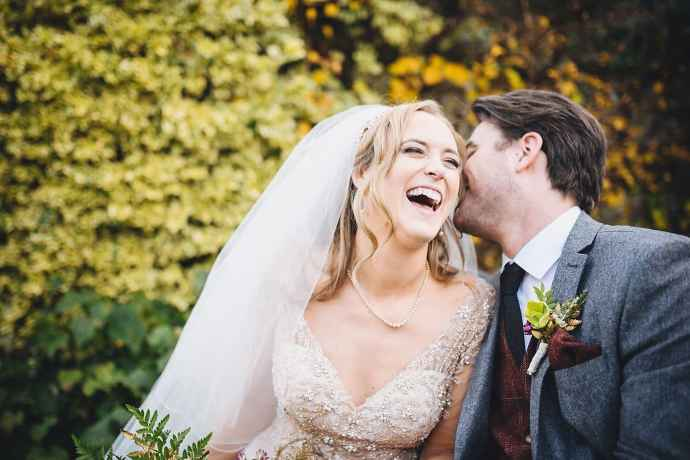 The groom whispers something in his bride's ear, and she bursts out laughing