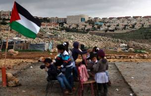 Niñas y niños de Abu Al-Nawwar (periferia de Jerusalén) después de que su escuela fue demolida. Detrás, las modernas construcciones de la Jerusalén judía.