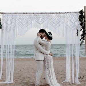 couple de mariés sur la plage, arche, décoration macramé, robe de mariée transparente, costume marié en lin