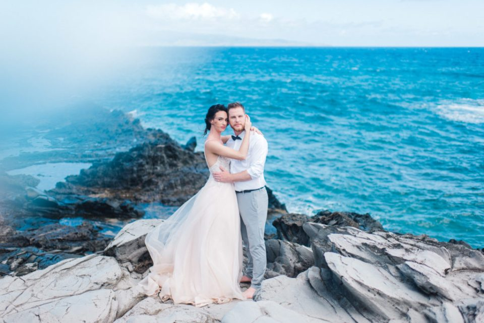 Maui elopement along lava rock cliffs featuring blue water and a gorgeous wedding gown