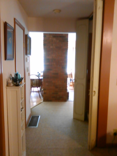 I used to be a hall, now I'm an arch in the wall. With a chimbley at the end, dividing the kitchen from the back room.