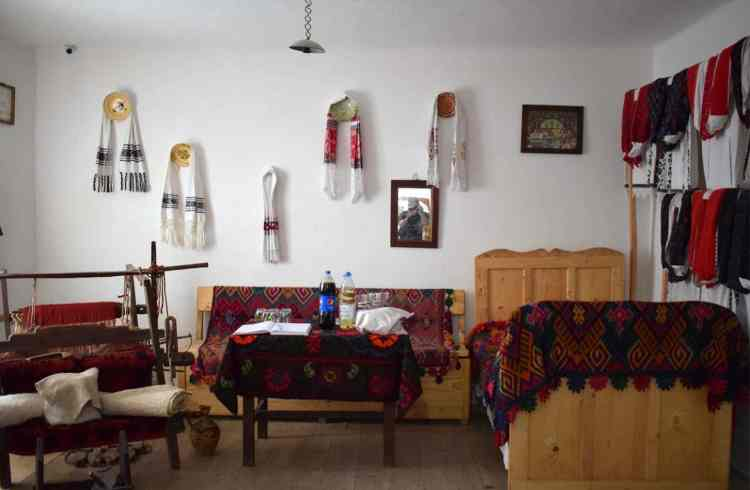 Traditional Romanian room with bed, table and loom and clothes for display