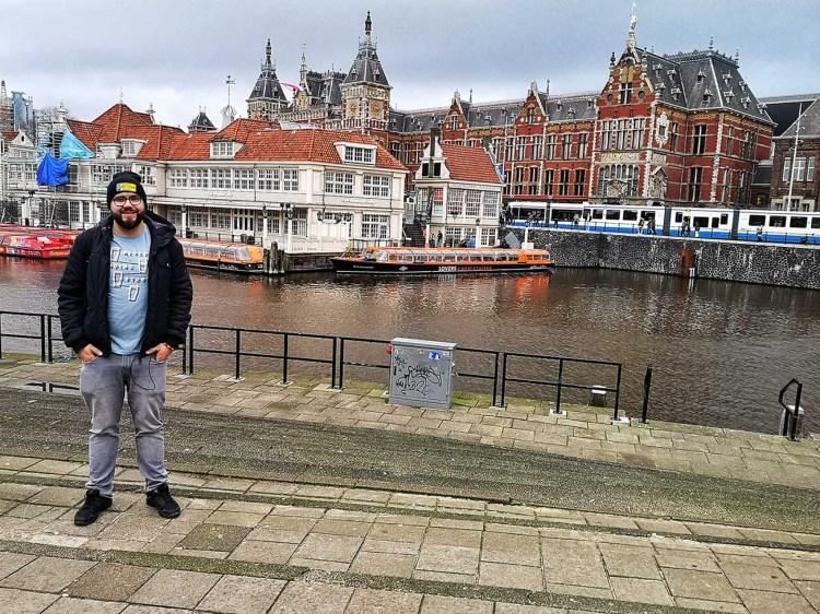 Eu, in AMsterdam, cu Gara Centrala si un canal in spate