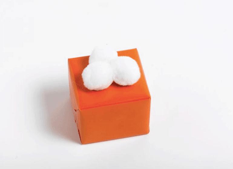 Ingeniørfruens enkle og fargerike gaveinnpakking i oransje med pomponger