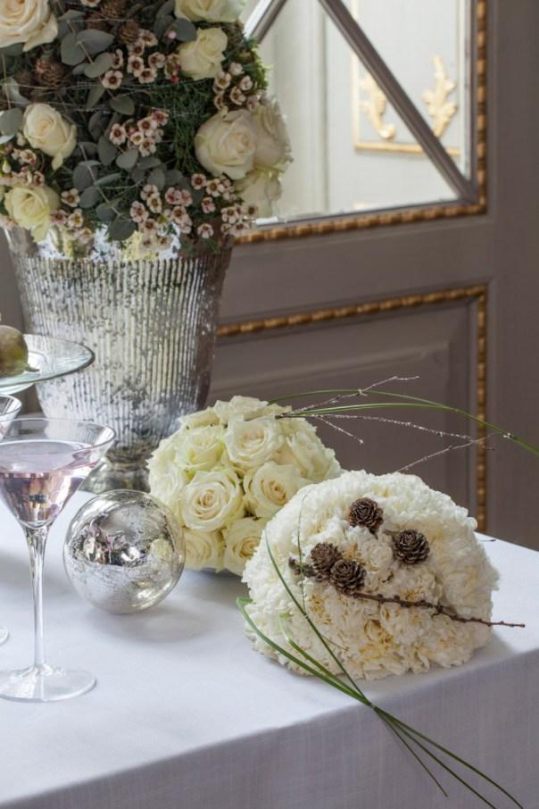 Kuler av hvite roser i oasis på nyttårsbordet