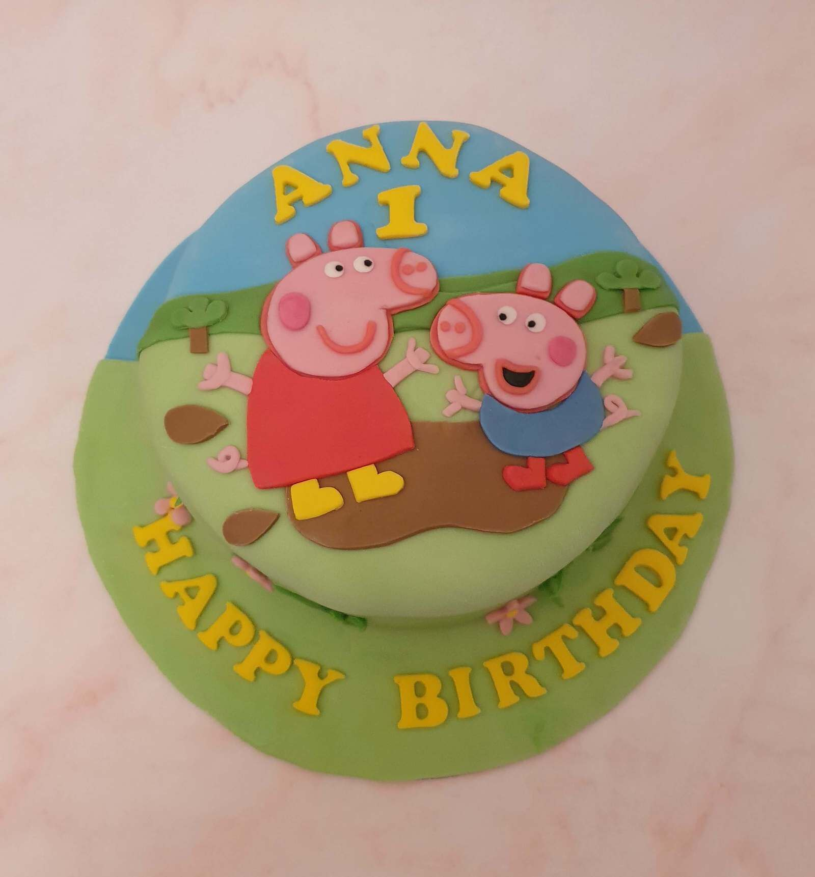 Peppa Pig and George splashing in a puddle in front of grass trees and blue sky on a 1st birthday cake that says happy birthday in yellow around the bottom