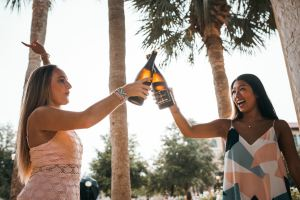 White woman and asian woman raise two wine bottles in a toast to illustrate Marie Deveaux's point that women can have it all if they start saying no to others and say yes to themselves more frequently.