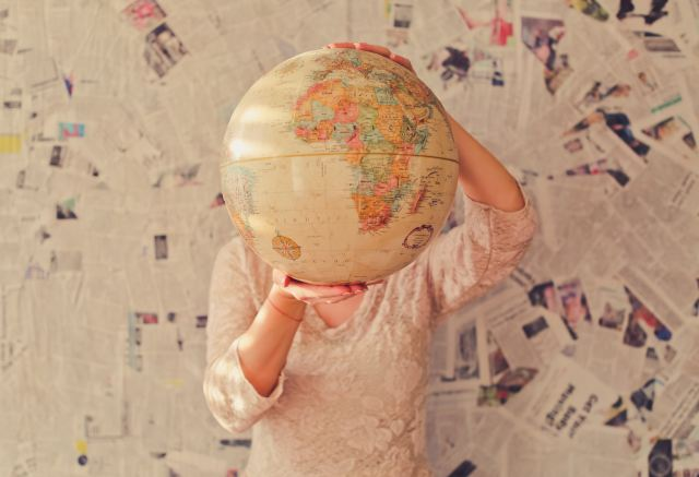 "A woman holds a globe in her hands covering her face agaisnt the backdrop of a wall cluttered in newsprint in an article by Marie Deveaux, bsuiness coach about women taking on too much because of the ""have it all"" mentality"