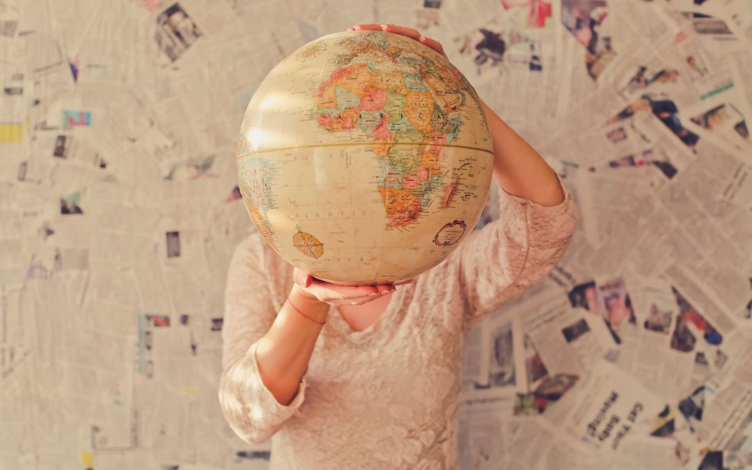 """A woman holds a globe in her hands covering her face agaisnt the backdrop of a wall cluttered in newsprint in an article by Marie Deveaux, bsuiness coach about women taking on too much because of the """"have it all"""" mentality"""