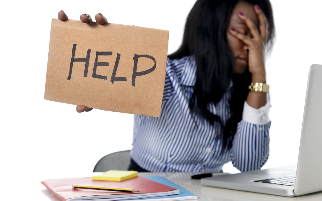 """Black business woman sitting at a desk over her laptop with cardboard """"help"""" sign as she buckels udner the weight of her responsibilities as a business owner. Image on mariedeveaux.com, career coaching for women of color."""