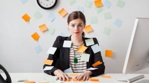 Woman covered in multi colored notes to illustrate the volume of responsibilities that entrepreneurs must meet each day. On mariedeveaux.com career coaching for women and minorities.
