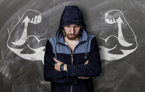Young man in hoodie looking shy and uncofident in front of a chalkboard displaying flexing biceps, featured on aritcle about Millennials' strength on mariedeveaux.com career coach site