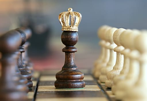 Image of a chess pon on the board between black and white wearing a golden crown related to work life balance article on mariedevaux.com career coaching site.