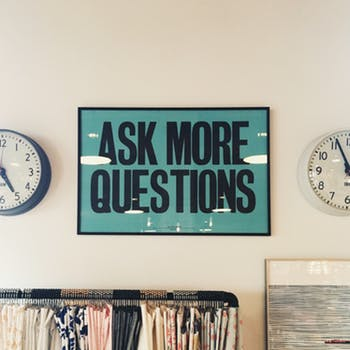 """""""ask more questions"""" poster featured in an office setting between two international clocks and a very full file cabinet. Featured on article about EQ and the One questions every manager should ask on mariedeveaux.com career coach"""