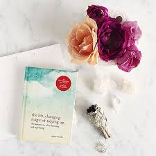 """Image of Marie Kondo's book the Life changing magic of tidying up displayed near a vase of vibrant flowers as featured in article """"Just say no"""" on mariedeveaux.com career coach"""