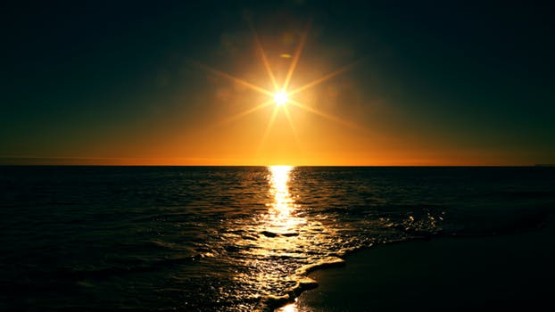 image of the sun rising over the water in article about early rising for increased productivity. From career coach, Marie Deveaux on mariedeveaux.com