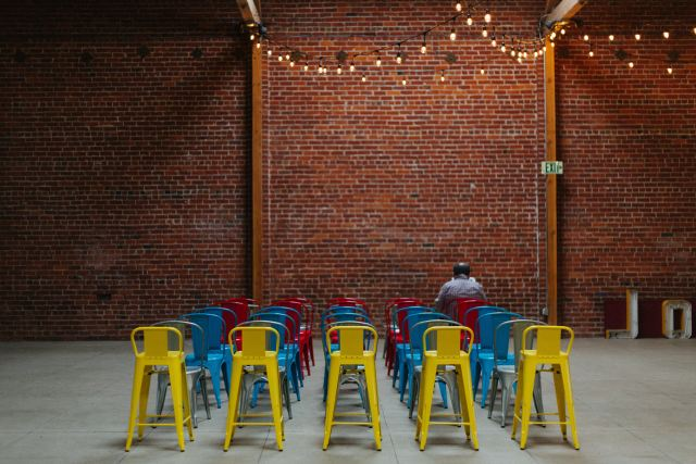 One seated person in a room full of colorful chairs illustrates the virtue of less connection when appropriate on Mariedevaux.com career coaching site. Photo by Kyle Glenn on Unsplash