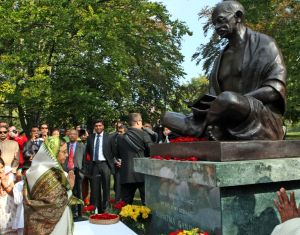 A group of people pray before a statue of Gandhi, illustrating the bias we have towards people of color's prejudices and biases as described by career coach, Marie Deveaux.