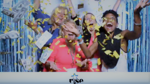 Marie Deveaux Career Coach is pictured with 3 other women in business casual attire, all smiling and laughing as yellow confetti and million dollar bill notes float down around them at the entrepreneur women network conference held in Dallas 2018