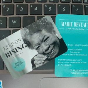 "Marie Deveaux's business card featuring a black and white photo of Maya Angelou smiling next to the words ""keep on rising"" and the company graphic and tagline ""you are a high tide"" lay across a black and silver laptop keyboard."