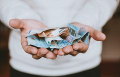 Marie Deveaux, career coach discusses how to break free from the work for money mindset and shift to working for good, with a photograph of a man with both hands outstretched cradling several european notes and other colorful currency.