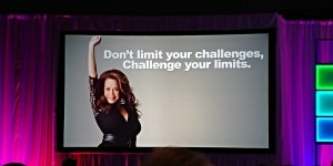 "Image of Sandra Yancey fist raised against a gray background with the words ""don't limit your challenges, challenge your limits"" written in white lettering over her head. View from Marie Deveaux's seat in the plenary sessions at the Ewomen network conference in 2018. The network for women empowers entrepreneurs to better serve their communities."