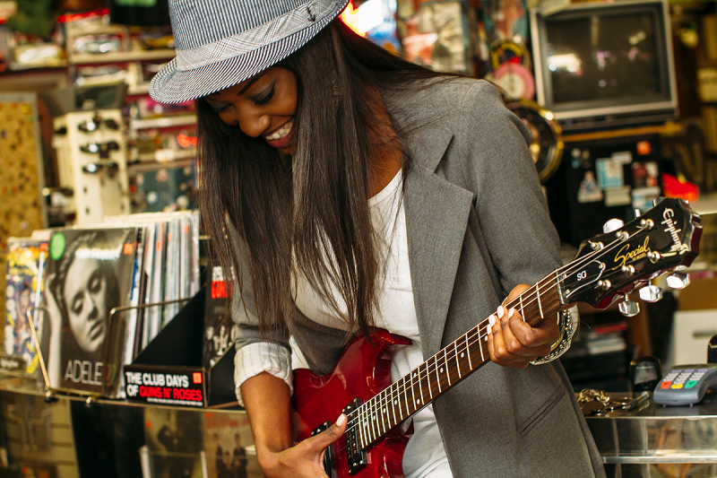 Black woman playing a red electric guitar in a record shop