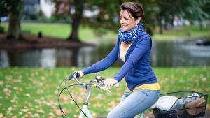 Marijana fährt mit einem Fahrrad an der Natur vorbei.