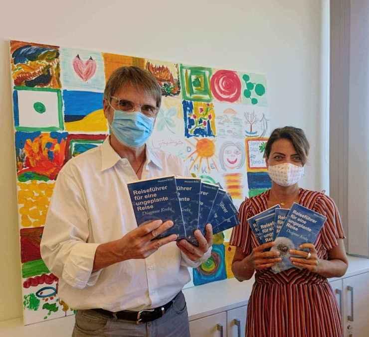 Marijana Brdar zeigt sich Mund- und Nasenschutz bezüglich ihrer Buchspende. Sie hält 3 Bücher in der Hand.