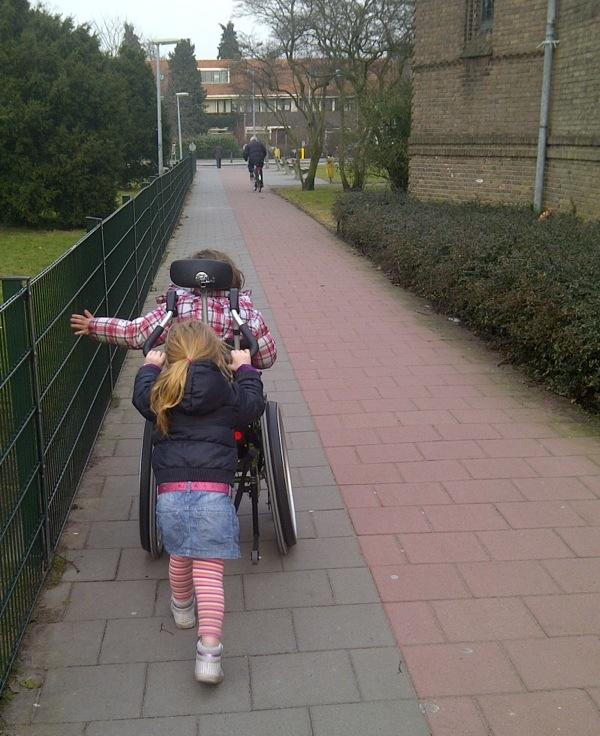 Zus duwt haar zus in de rolstoel. Mantelzorg!