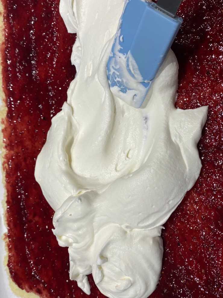 Spread the whipped cream over the jam