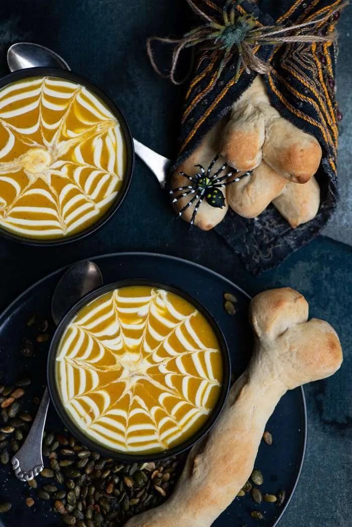 Græskarsuppe er perfekt til Halloween. Lav et fint spindelvæv på toppen og server suppen med koglebrød og ristede græskar. Selve suppen er lavet på ovnbagte græskar og æbler og er tilsat kokosmælk. En lækker og mild græskarsuppe som børn elsker uden at den bliver kedelig for voksne. Opskrift og DIY på spindelvæv fra Marinas Mad.