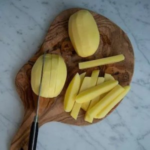 På billedet kan man se hvordan kartoflerne skærpes i stave