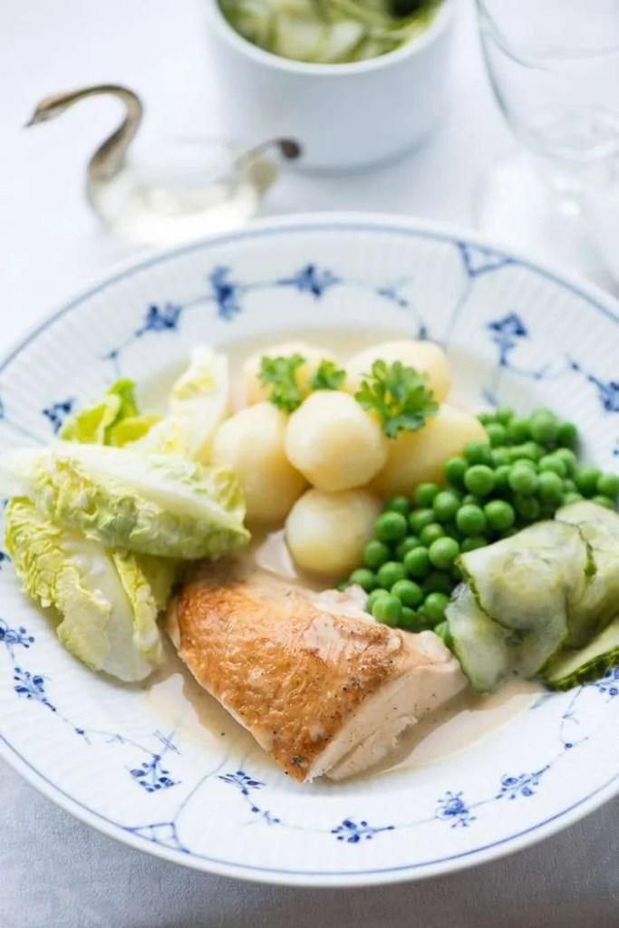 Grydestegt kylling med skilt sovs serveret med nye kartofler og agurkesalat. Billedet er med musselmalet talerken og svanesaltkar for at illustrerer det danske.