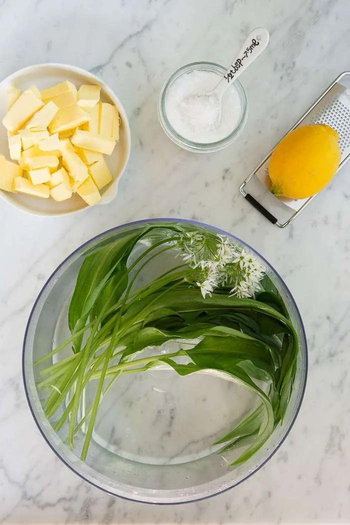 Alle ingredienser til ramsløgssmør: smør i små tern, ramsløg og ramsløgsblomster der bliver skyllet i en stor skål med vand, flagesalat og en økologisk citron på rivejern.