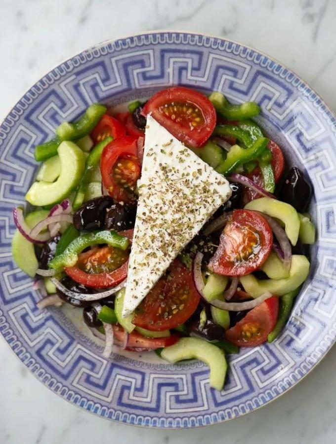Den autentiske Horiatiki salat set oppefra så man kan se grøntsagerne og fetaosten drysset med oregano