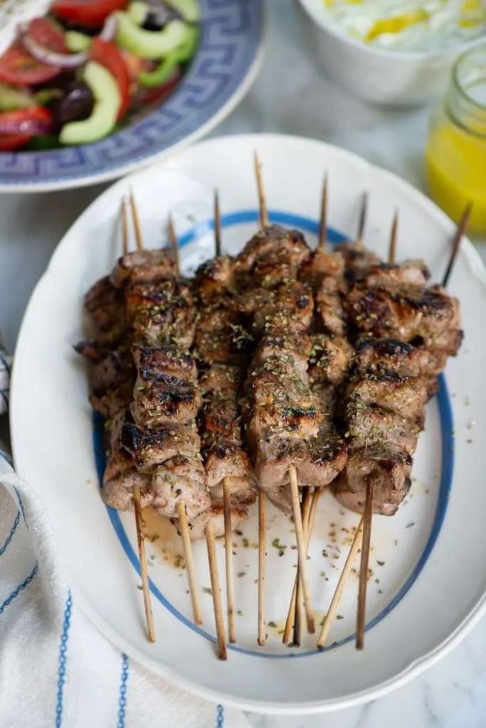 De færdige souvalaki spyd i baggrunden græsk salat og græsk ladolemono dressing
