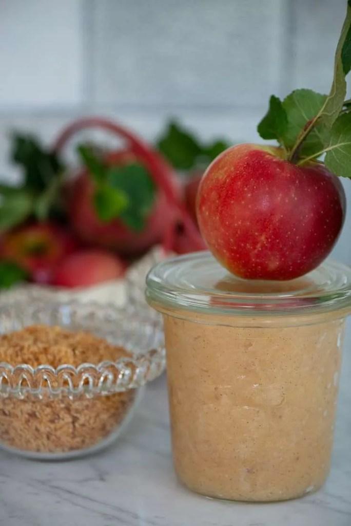 Æblemos til gammeldags æblekage, med æblekagerasp i en skål ved siden af. Desuden smukke røde æbler