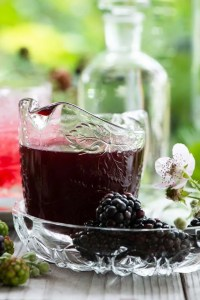 Brombærsirup med sukkersirup og en Bramble drink i baggrunden