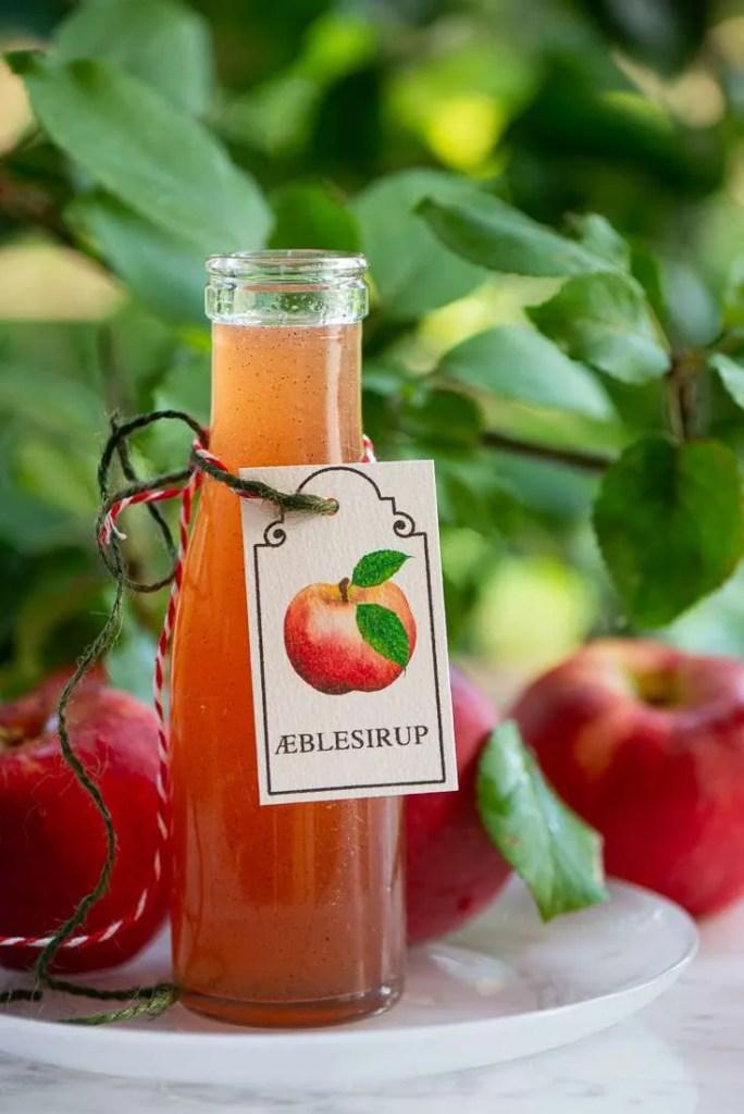 Den smukke æblesirup med vanilje omgivet af de røde æbler der har givet den farven