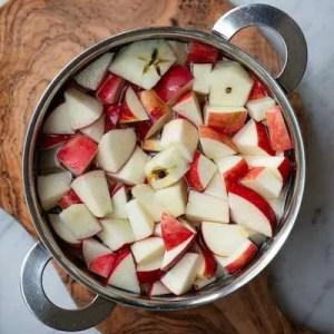Æbletern i gryden dækket med vand. Man kan se at der er brugt kernehus og æbleskræller